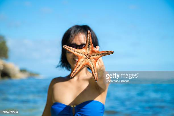 Woman in bikini holding a starfish in front of her face