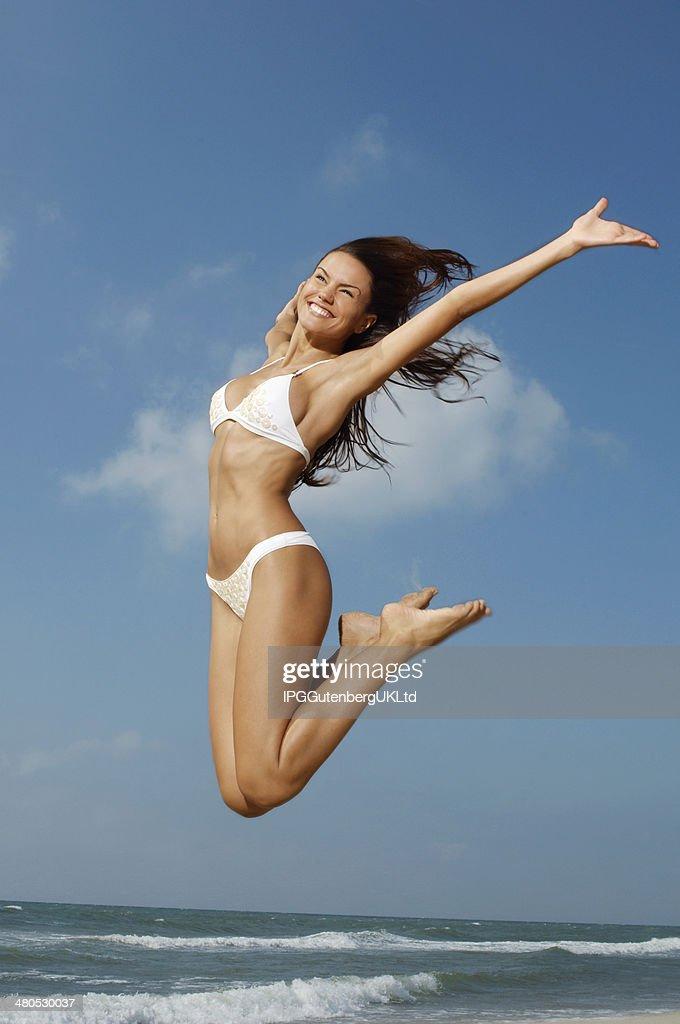 Woman In Bikini Jumping Midair On Beach : Stock Photo