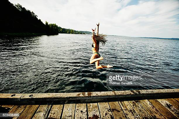 Woman in bikini jumping off of dock into lake