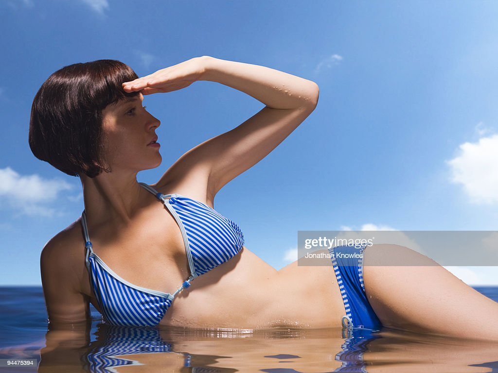 Woman in bikini laying in ocean and shielding eyes : Stock Photo