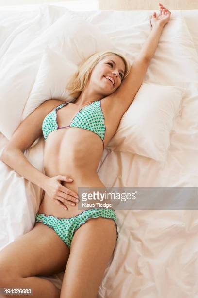 Woman in bikini laying on bed