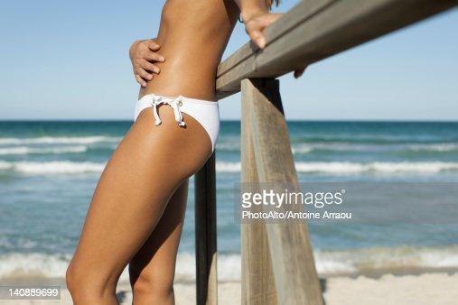 Woman in bikini leaning against railing at the beach, cropped