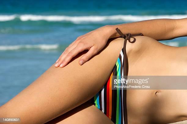 Woman in bikini lying on side, mid section