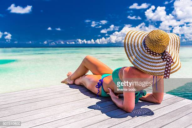 Woman in bikini on a tropical beach at Maldives, tranquil background