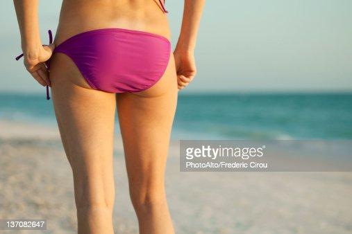 Woman in bikini on beach, rear view