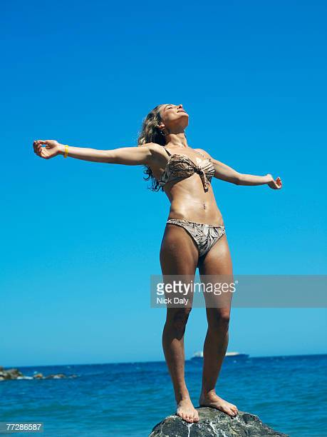 Woman in bikini posing on rock by ocean