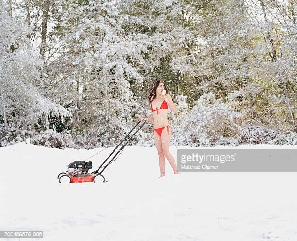 Woman in bikini pushing lawn mower in snow, eating ice cream