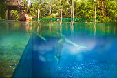 beautiful woman relaxing in a gorgeous tropical bright blue pool(side view)