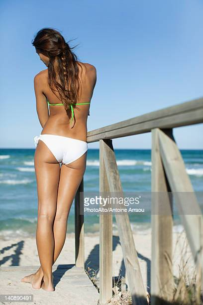 Woman in bikini relaxing on beach, looking at sea