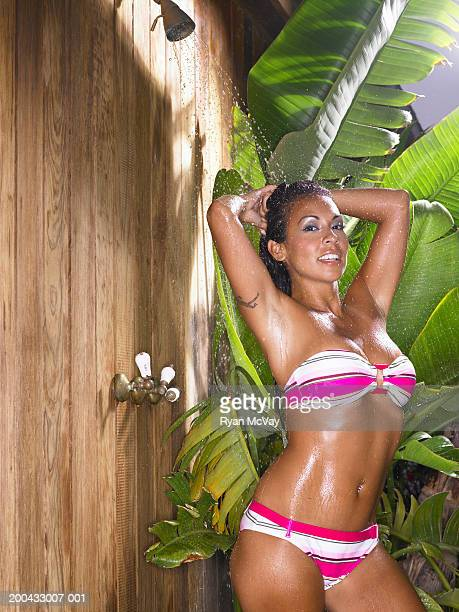 Woman in bikini showering outdoors, hands behind head, portrait