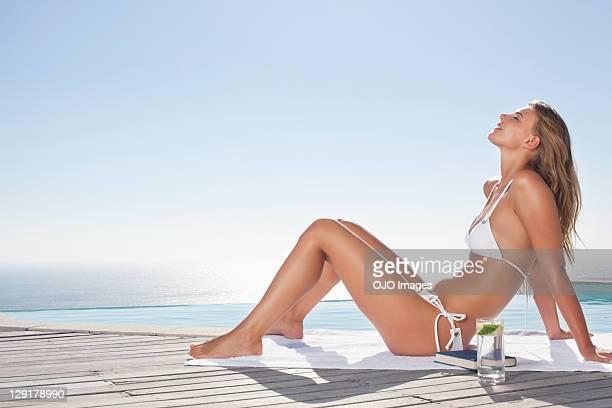 Femme en bikini assis sur le bord de la piscine
