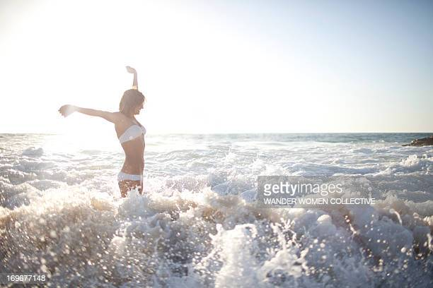 Woman in bikini splashing and jumping  beach waves