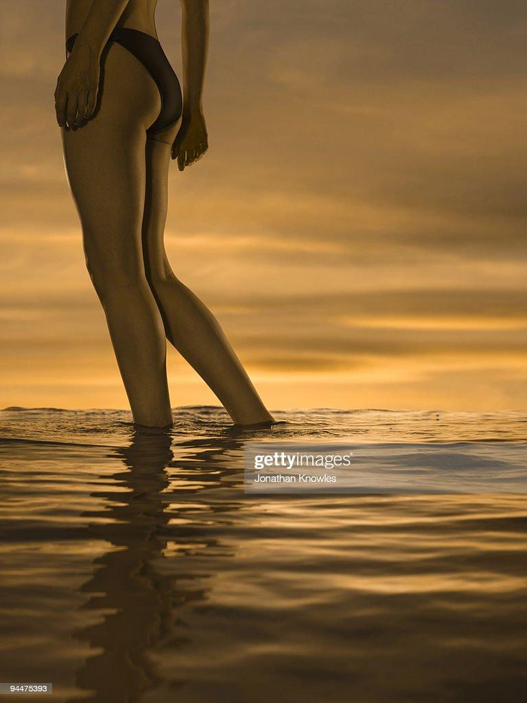 Woman in bikini standing in ocean at sunset : Stock Photo