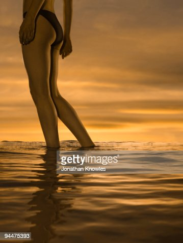 Woman in bikini standing in ocean at sunset : Foto de stock
