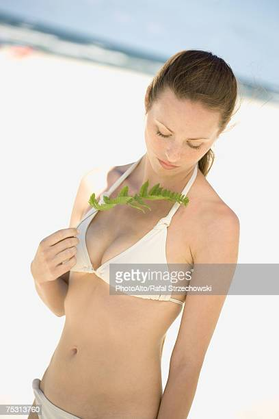 Woman in bikini standing on beach, holding up leaf, waist up