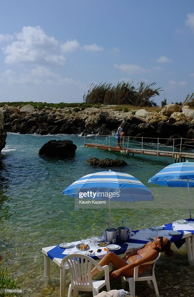 A woman in bikini sun bathes at the beach in Jammal sea food restaurant on July 18, 2013 in Batroun, Lebanon. Despite the rising tensions between different Muslim factions in the country people enjoy their leisure time and continue their daily life as normal.