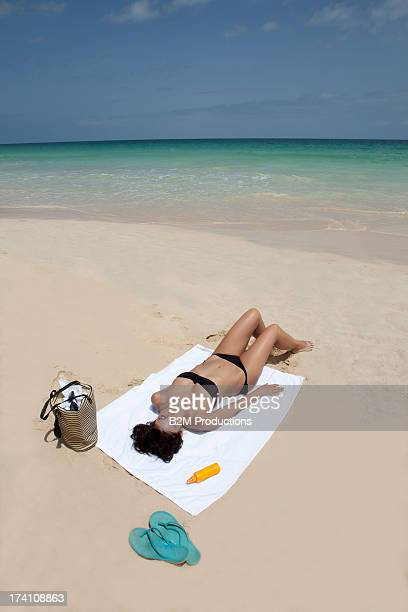 Woman In Bikini Sunbathing At Beach