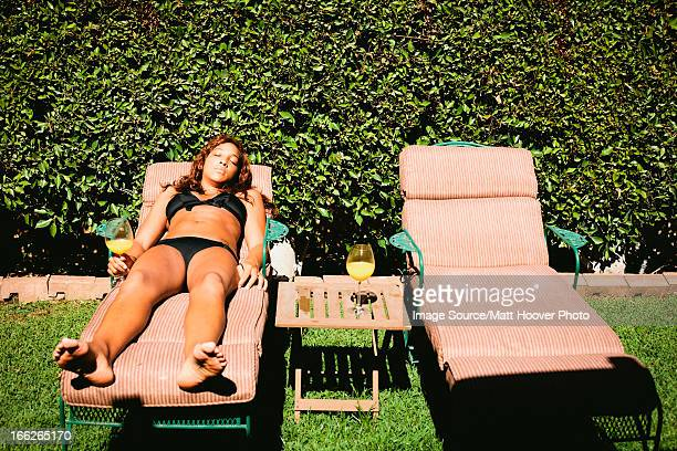 Woman in bikini sunbathing in lawn chair