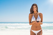 Young woman in white bikini holding smartphone and looking at camera. Beautiful latin girl using mobile phone at beach. Smiling brunette woman enjoying at beach while typing on cellphone.