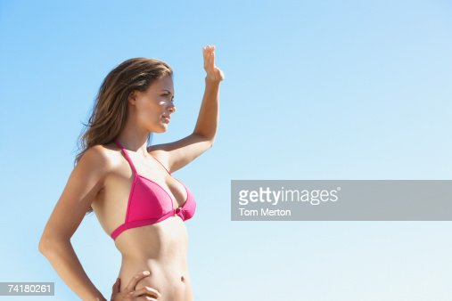 Woman in bikini waist up blocking sun with hand : Stock Photo
