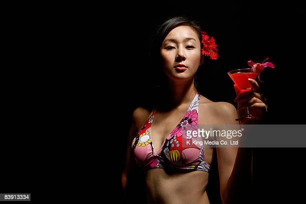 Woman in bikini with cocktail.