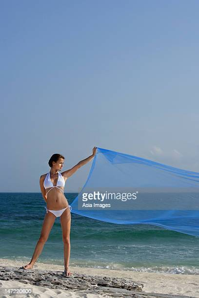 woman in bikini with flowing blue fabric
