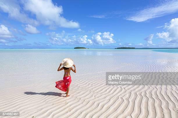 Woman in bikini with sarong in turquoise lagoon
