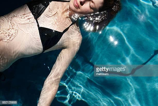 Woman in black bikini floats in swimming pool