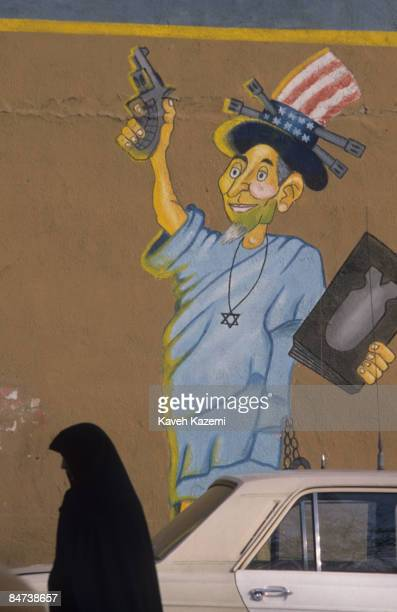A woman in black chador passes an antiAmerican mural in Tehran with a caricature of Uncle Sam in the pose of the Statue of Liberty wearing a Star of...