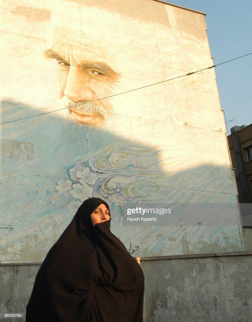 A woman in black chador passes under a huge mural depicting Ayatollah Ruhollah Khomeini in Vanak square, in northern Tehran, 8th December 2003.