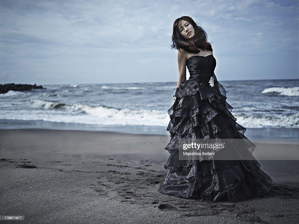 Woman in black dress at sea beach. : Stock Photo