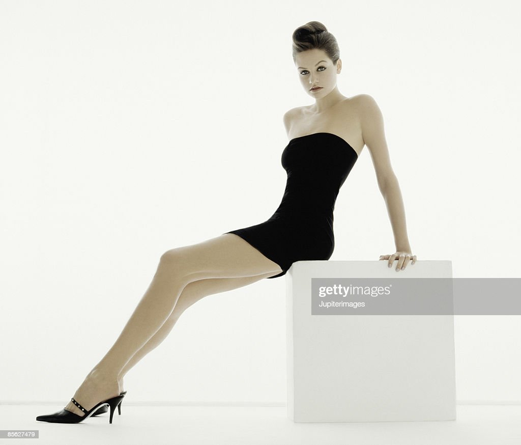 Woman in Black Dress Seated on White Cube : Stock Photo