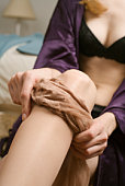 Woman in black lace underwear, putting on stockings in bedroom