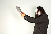 woman in black with white make holding knife on white background.