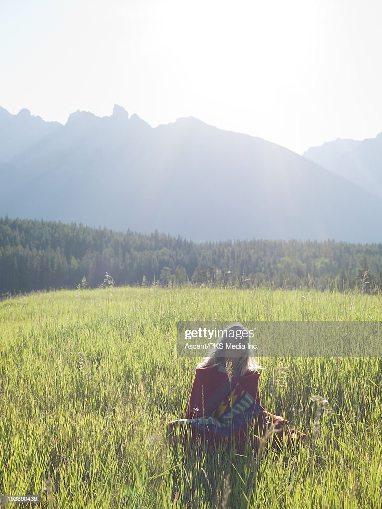 Woman, in blanket, relaxes in mountain meadow : Stock Photo