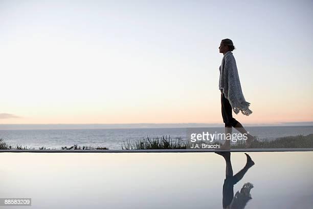 Woman in blanket walking near swimming pool