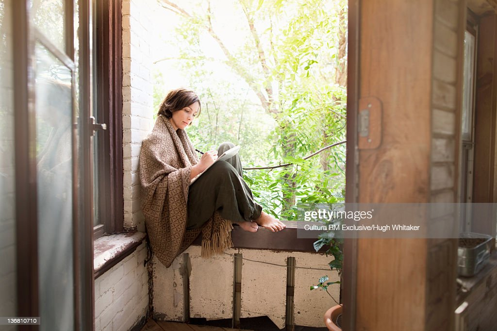 Woman in blanket writing on balcony : Stock Photo