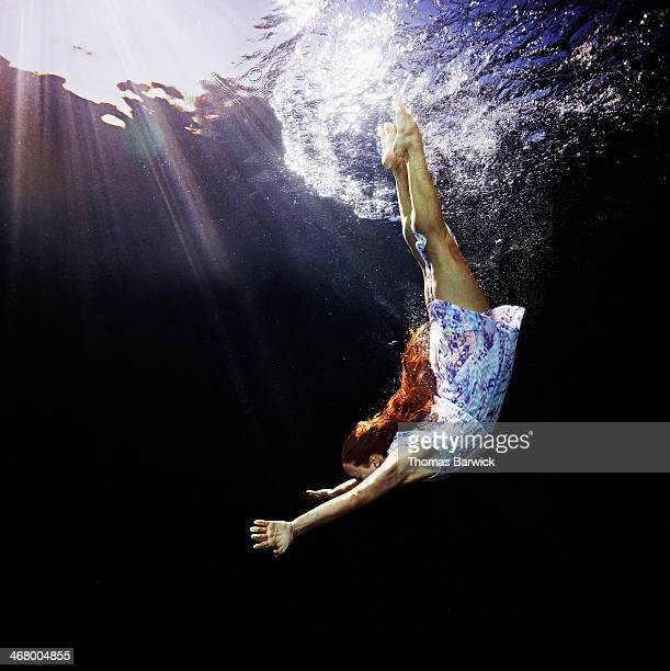 Woman in blue dress diving underwater