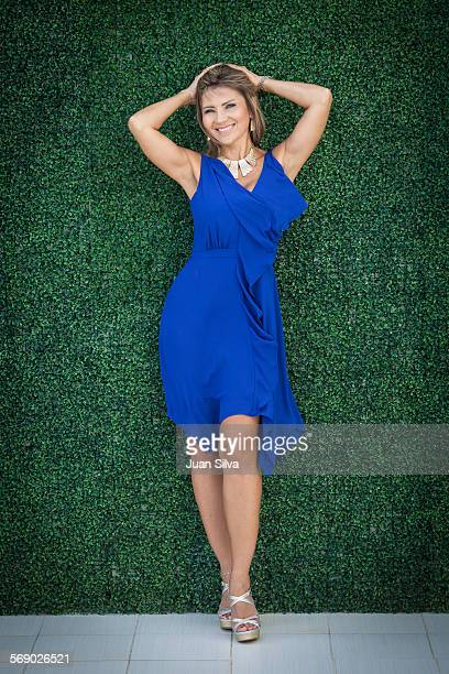 Woman in blue dress standing by ivy wall