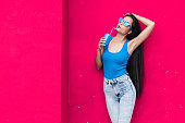 Woman in blue vest and sunglasses in front of pink wall background holding red can