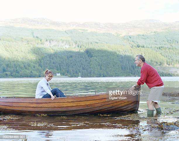 Woman in boat being pushed by man, smiling