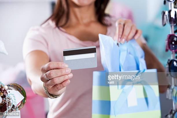 Donna in boutique con carta di credito e shopping bag