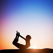 Woman in bow yoga pose meditating at sunset. Zen, meditation, peace
