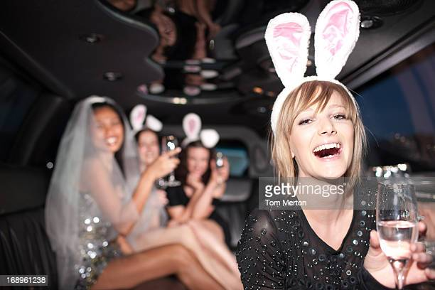 Woman in bunny ears drinking champagne in limo