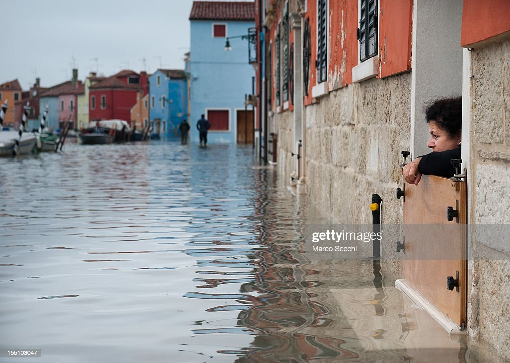 A woman in Burano watches the rising tide on November 1, 2012 in Venice, Italy. More than 59% of Venice has been been left flooded, after the historic town was hit by exceptionally high tides. The sea level rose above 140cm overnight was expected to remain above critical levels for about 15 hours.