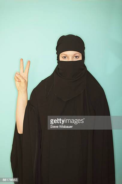 Woman in burka making peace sign gesture