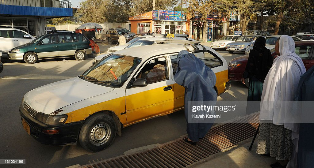 A woman in burka takes a yellow-white taxi on the street on October 18, 2011 in Kabul, Afghanistan.