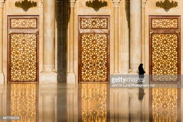 Woman in burka walking by ornate Saleh Mosque