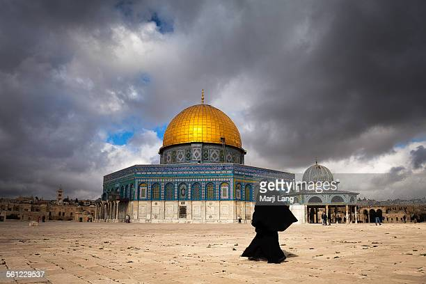 Woman in burqa by dome of the rock in Jerusalem