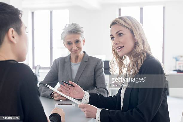 Woman in business meeting talking to two female colleagues